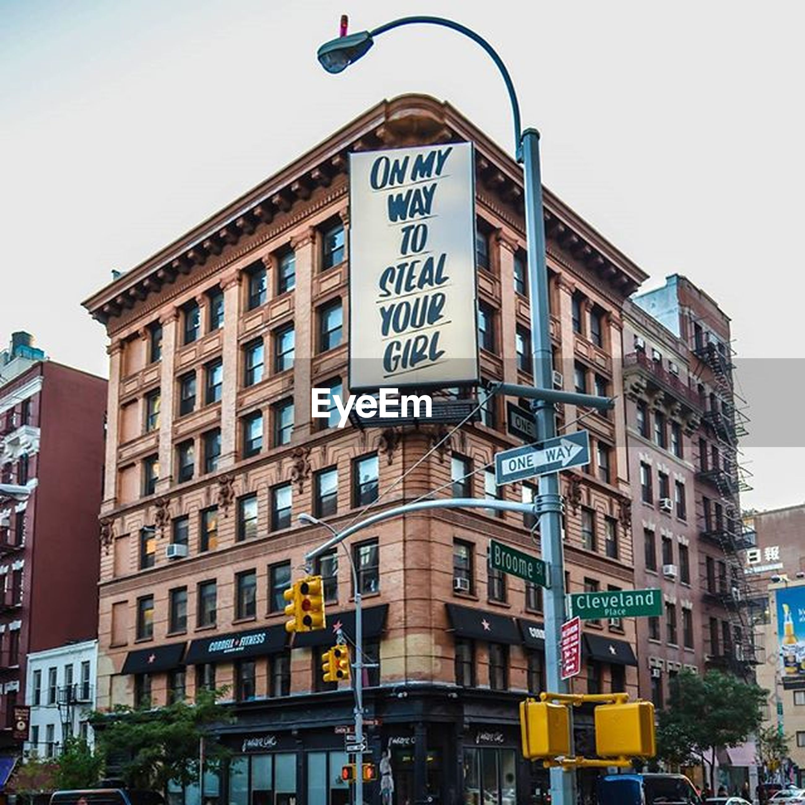 building exterior, architecture, built structure, text, city, low angle view, western script, road sign, car, street, communication, information sign, transportation, clear sky, building, city life, land vehicle, non-western script, street light, sky