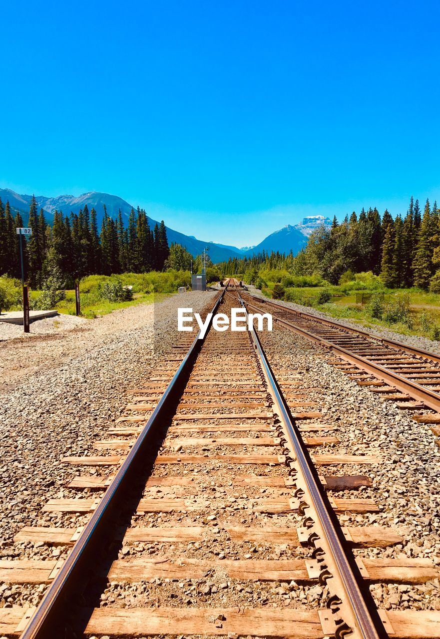 rail transportation, railroad track, track, sky, transportation, direction, the way forward, blue, nature, clear sky, tree, diminishing perspective, plant, no people, vanishing point, day, scenics - nature, mountain, beauty in nature, copy space, straight, long, parallel