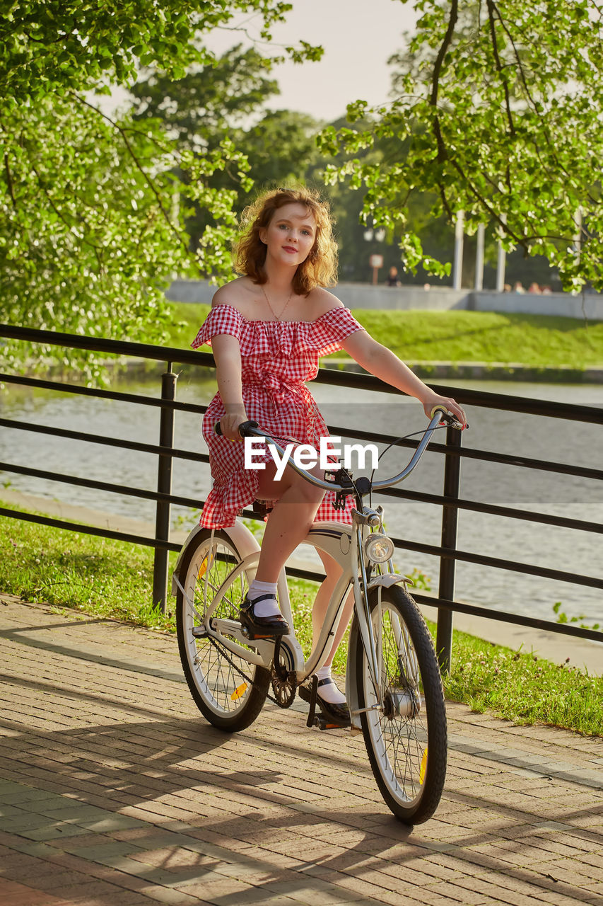 PORTRAIT OF SMILING YOUNG WOMAN RIDING BICYCLE ON TREE