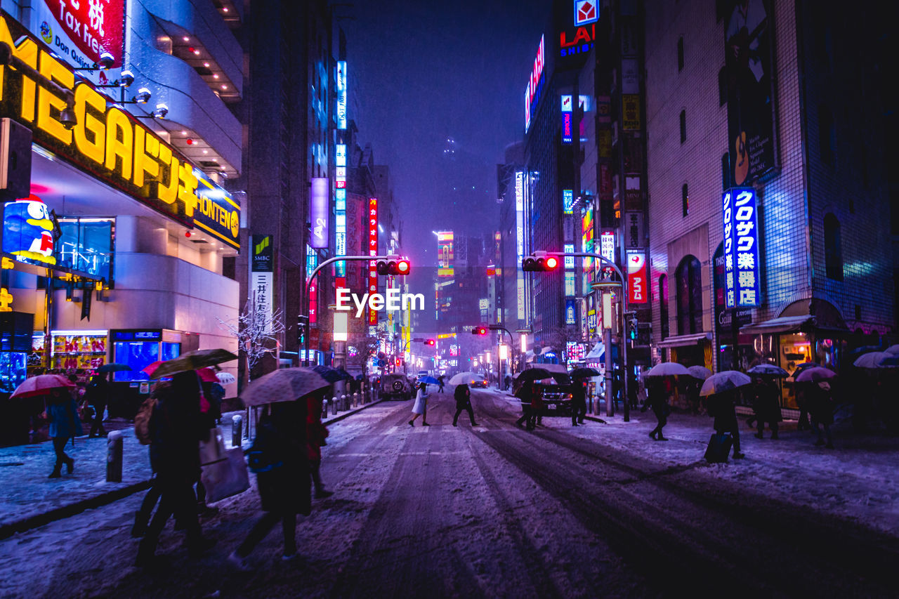 People Walking On Illuminated Street Amidst Buildings During Snowfall