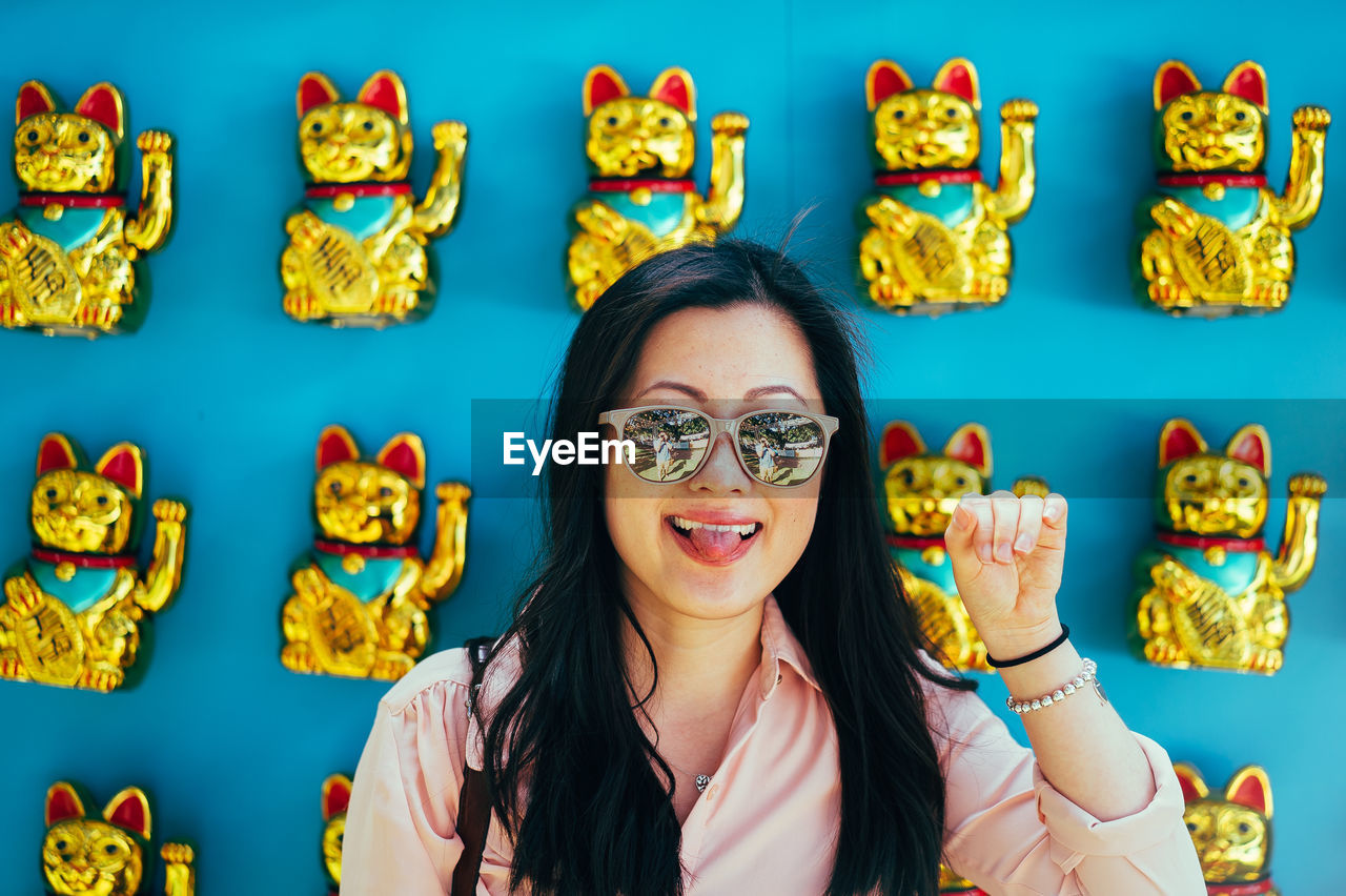 Close-Up Of Woman Wearing Sunglasses Against Maneki Neko
