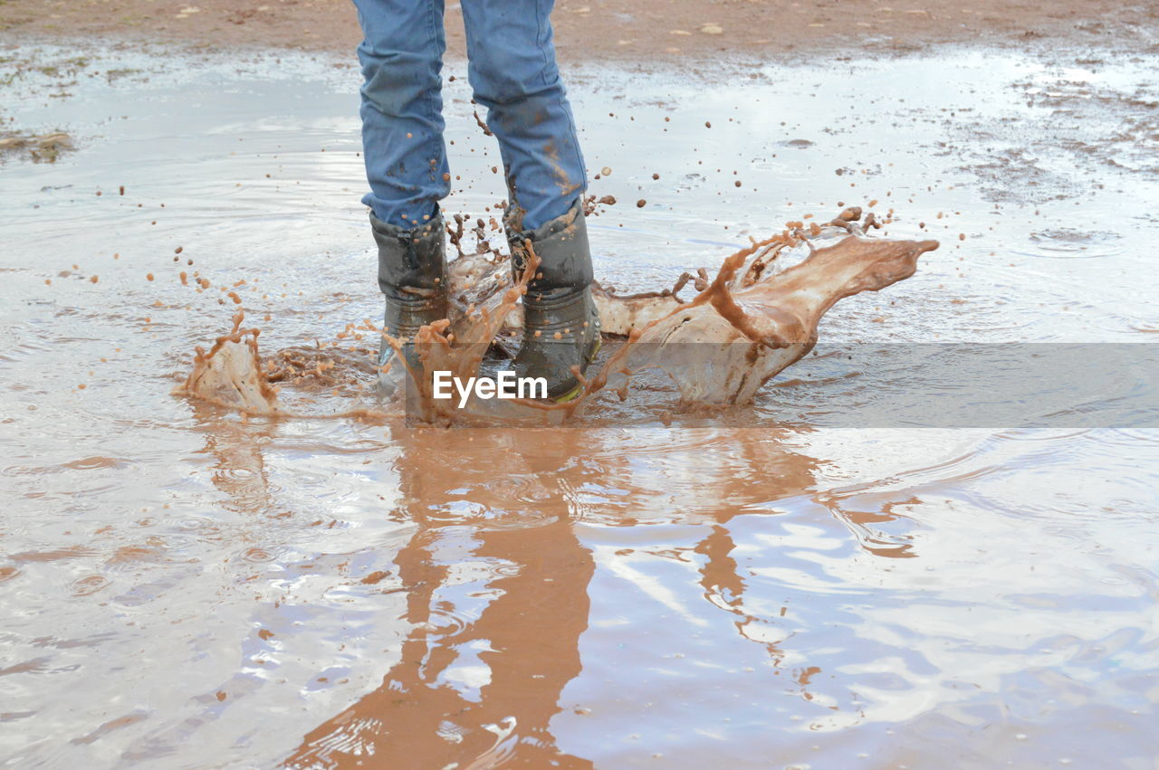 Low Section Of Person Splashing Muddy Puddle