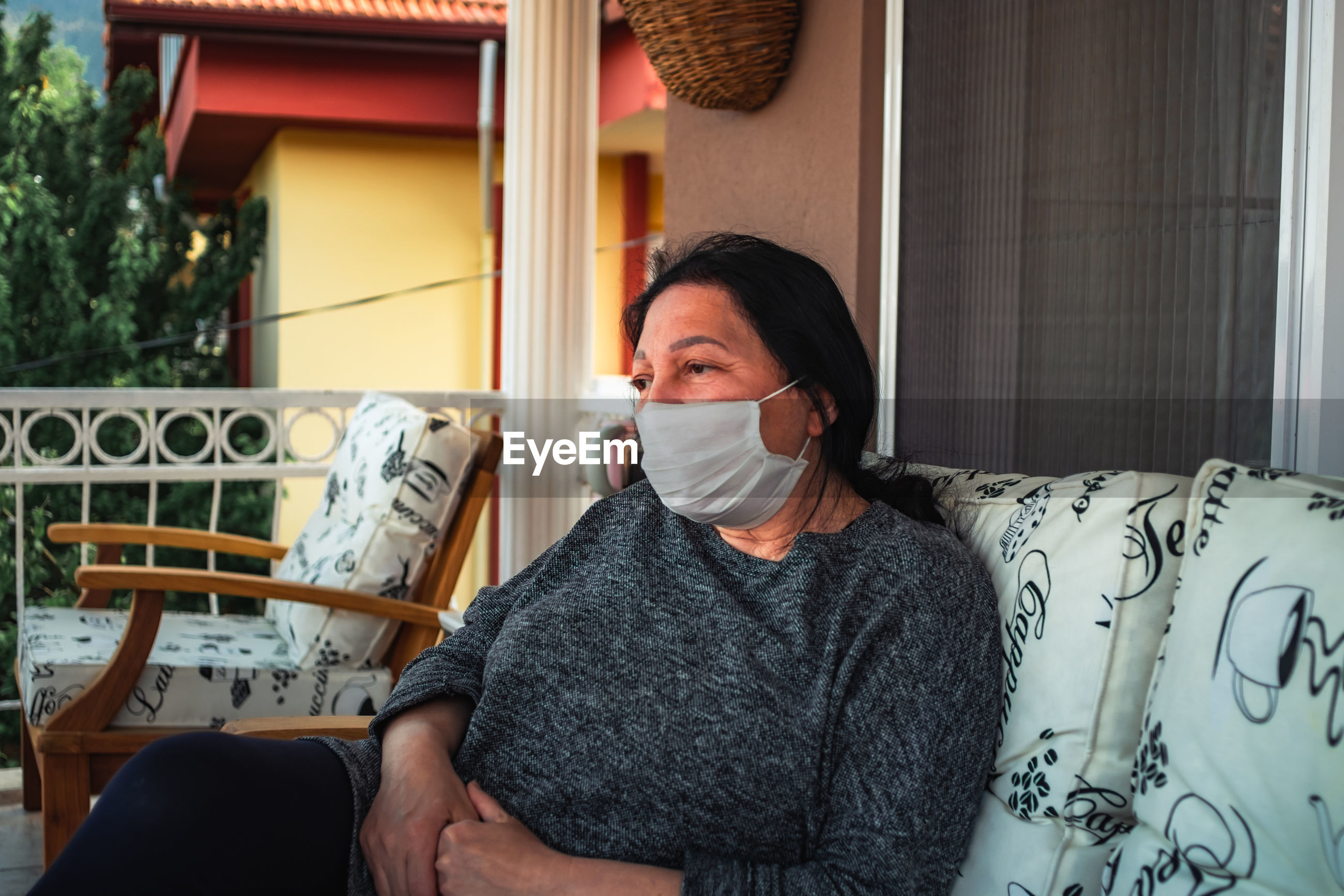 Middle aged caucasian woman with medical face mask, resting on cpuch on veranda during covid threat.