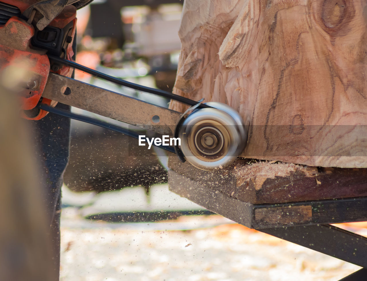 Cropped image of man using equipment on wooden sculpture