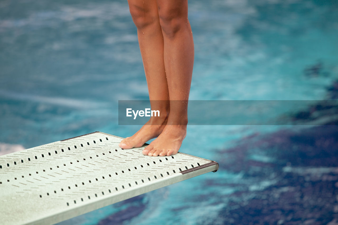 Low Section Of Woman Standing On Diving Board