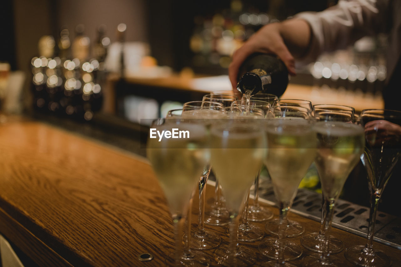 Cropped Image Of Bartender Pouring Wine In Glasses On Counter