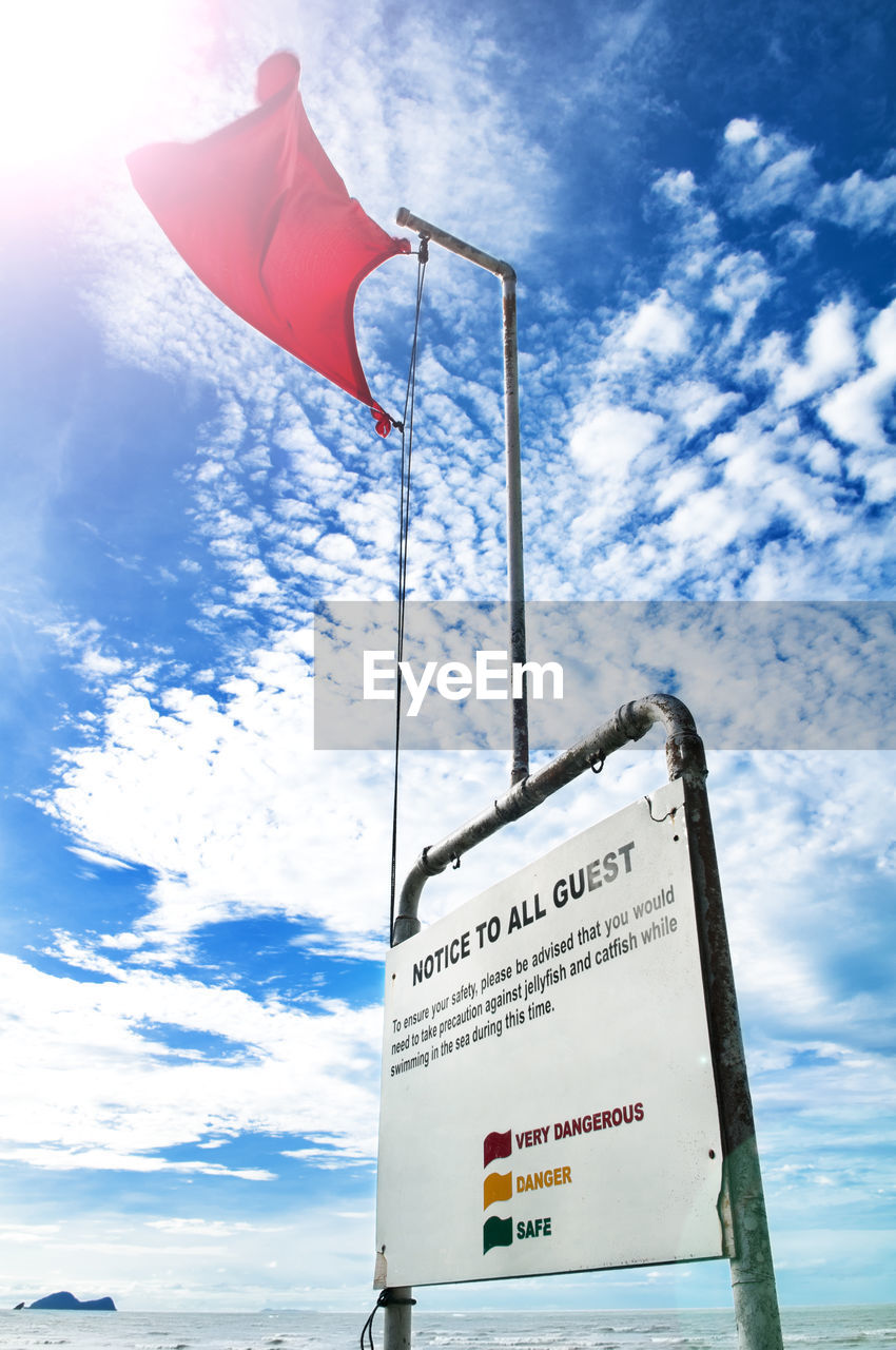 sky, low angle view, cloud - sky, western script, text, nature, day, flag, communication, red, patriotism, no people, sign, non-western script, script, sunlight, guidance, symbol, outdoors, pole, message