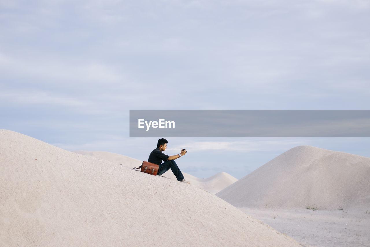 Full length of man on sand dune against sky