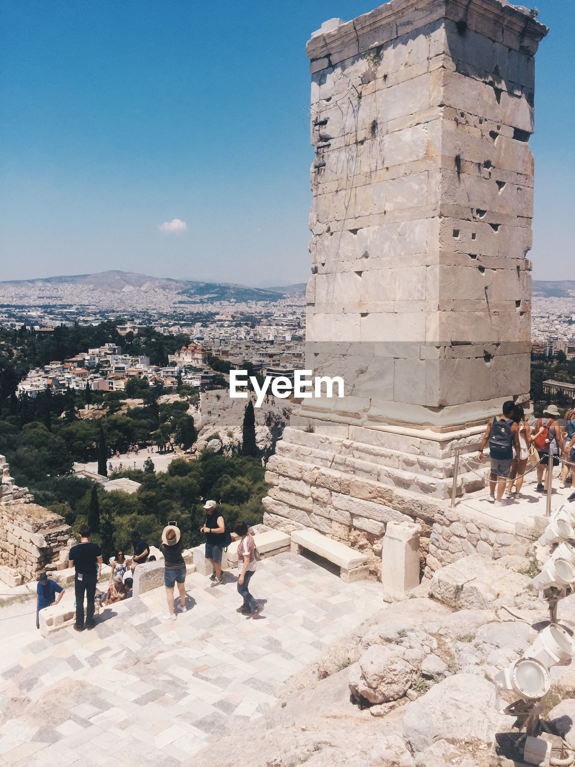 old ruin, history, built structure, architecture, ancient, travel destinations, ancient civilization, archaeology, tourism, travel, the past, large group of people, men, day, real people, building exterior, women, outdoors, architectural column, vacations, mountain, lifestyles, sky, adult, people