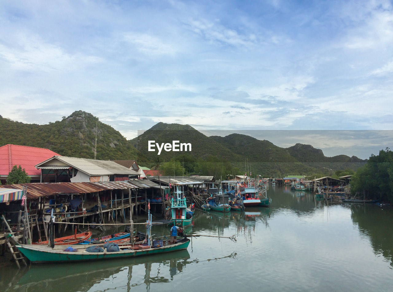 water, nautical vessel, mountain, sky, transportation, cloud - sky, building exterior, built structure, mode of transportation, architecture, nature, moored, waterfront, day, building, house, no people, reflection, beauty in nature, mountain range, outdoors, fishing boat
