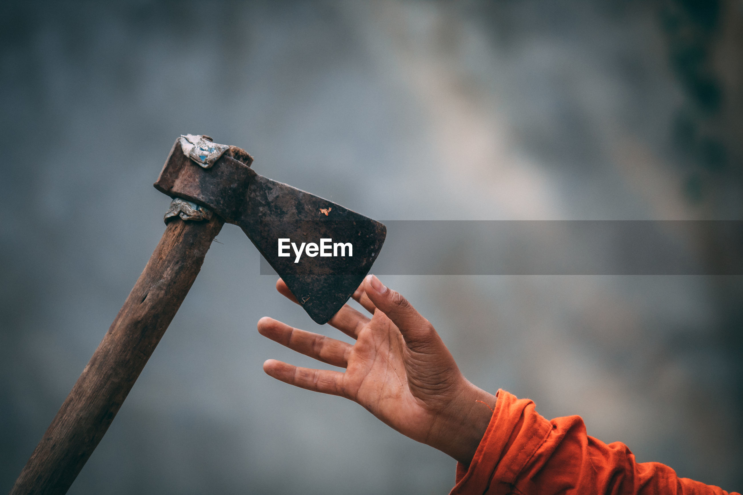Cropped hand reaching for axe against wall
