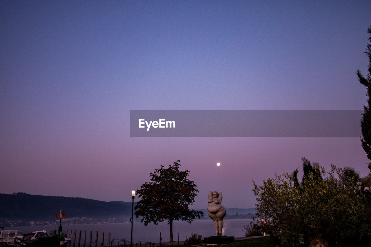 sky, tree, plant, nature, copy space, moon, no people, beauty in nature, blue, night, illuminated, clear sky, architecture, scenics - nature, outdoors, sunset, built structure, tranquility, dusk, silhouette, purple