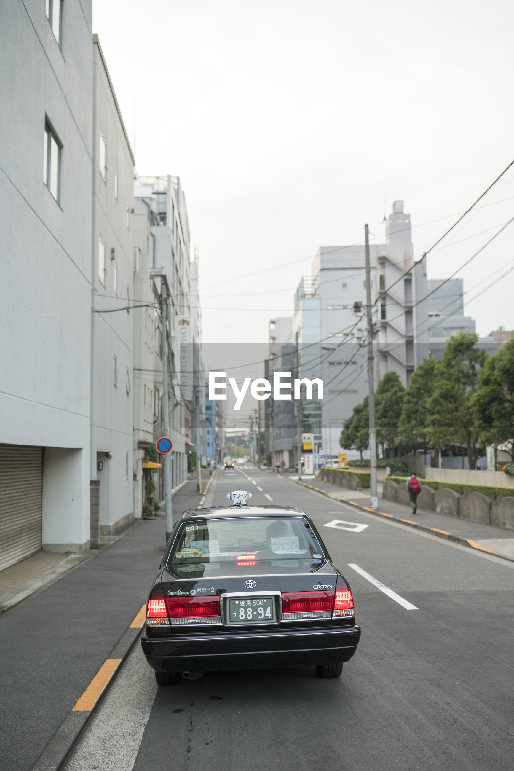 CARS ON STREET BY BUILDINGS AGAINST SKY