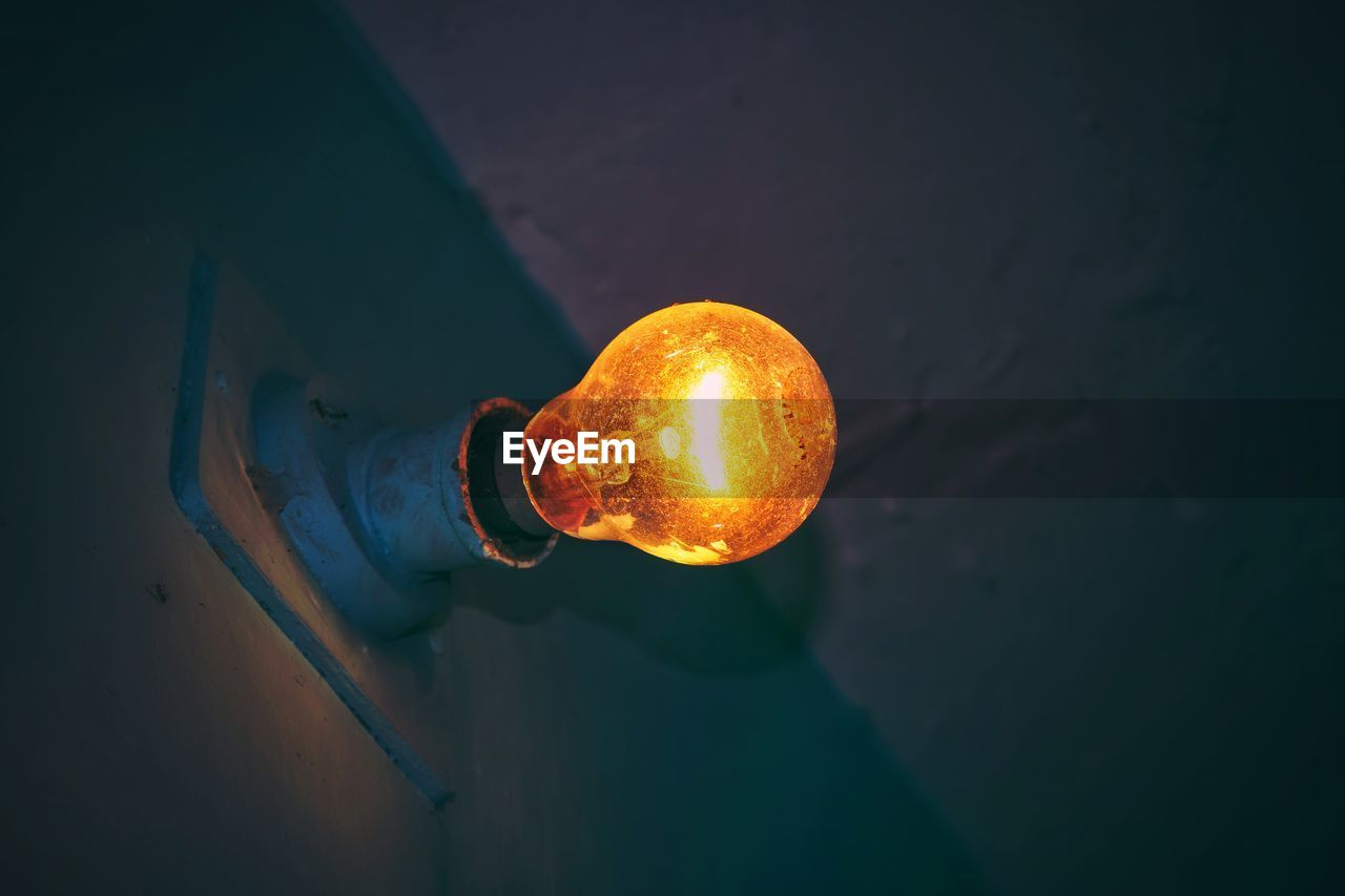 light bulb, illuminated, electricity, holding, one person, lighting equipment, indoors, fuel and power generation, close-up, men, heat - temperature, technology, skill, occupation, real people, hand, orange color, glass - material, power supply, light