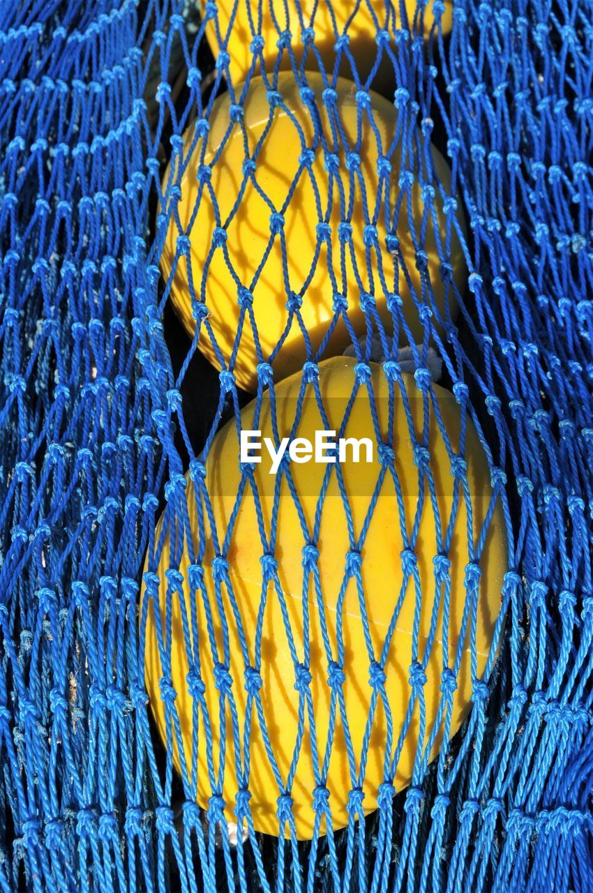 Close-Up Of Buoy By In Blue Fishing Net