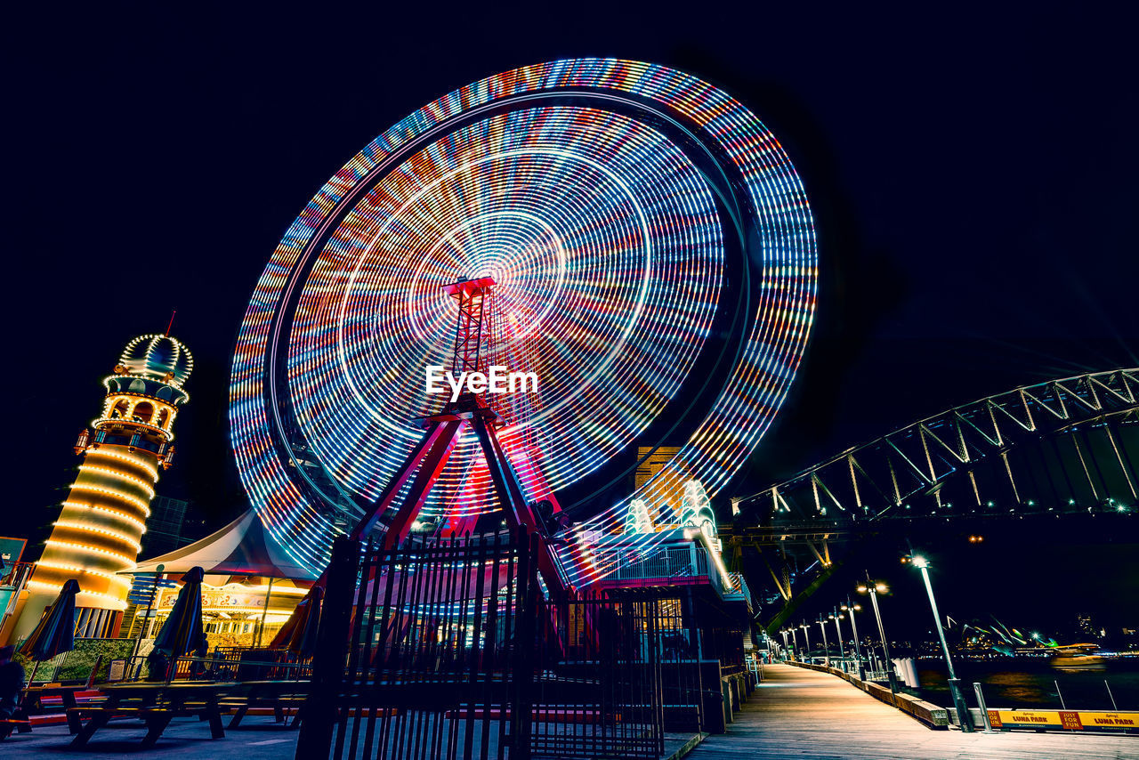 amusement park, amusement park ride, night, arts culture and entertainment, illuminated, ferris wheel, sky, architecture, built structure, no people, motion, nature, clear sky, low angle view, outdoors, travel destinations, multi colored, fairground, spinning, geometric shape
