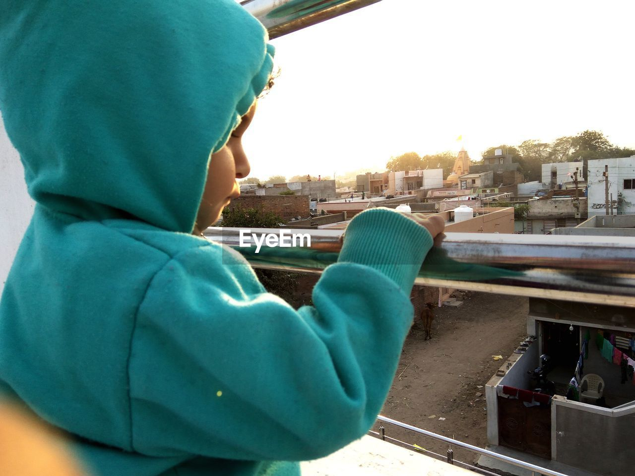 Close-Up Of Girl Looking Through Window Against Sky