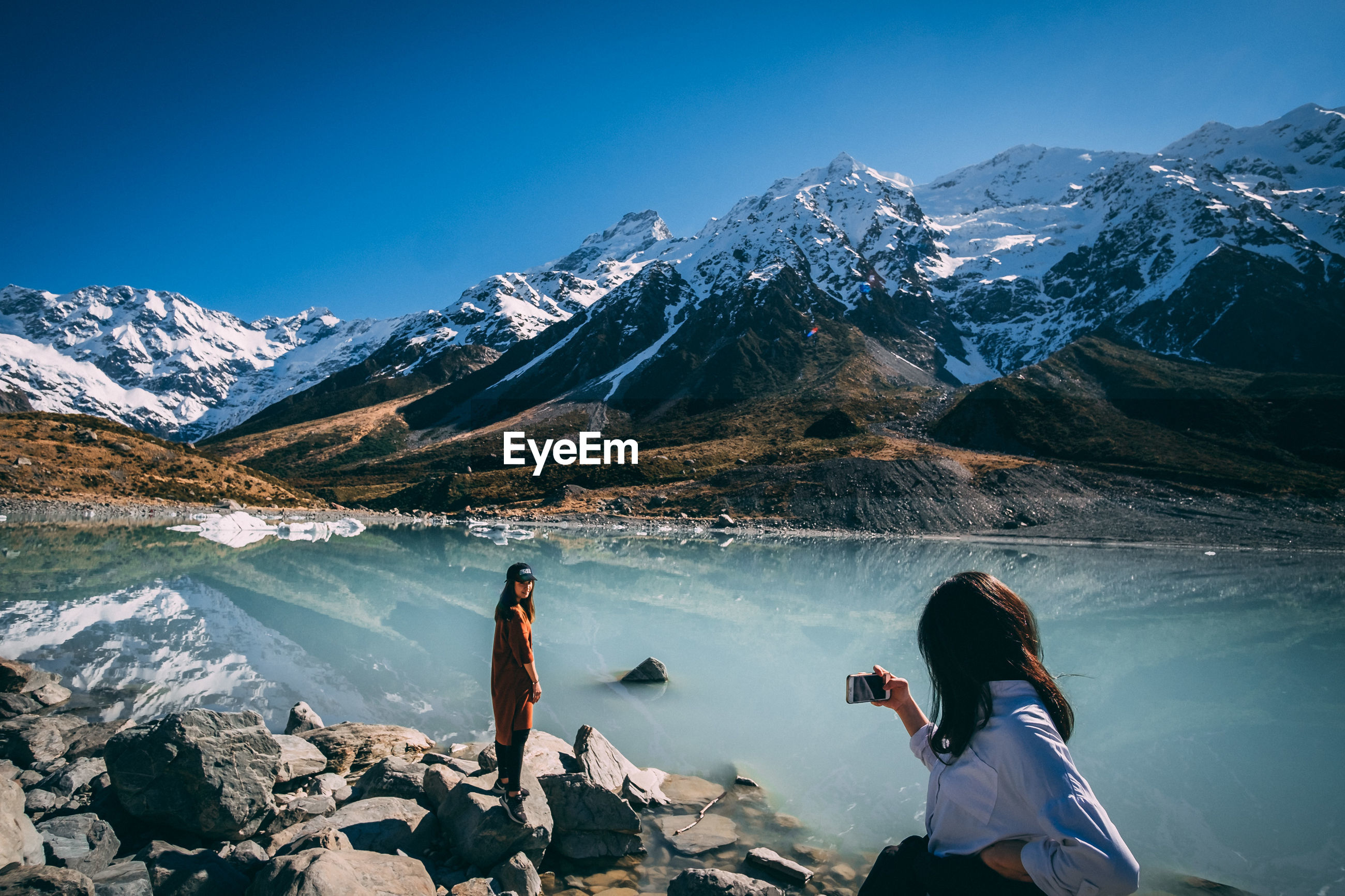 Girls taking photo with her smart phone next lake and snowcapped mountains