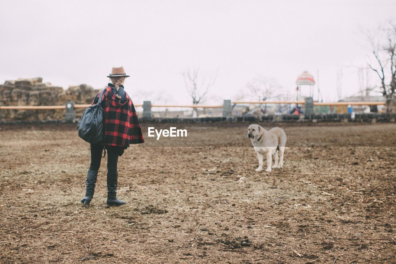 Rear View Of Cowgirl Standing In Front Of Dog