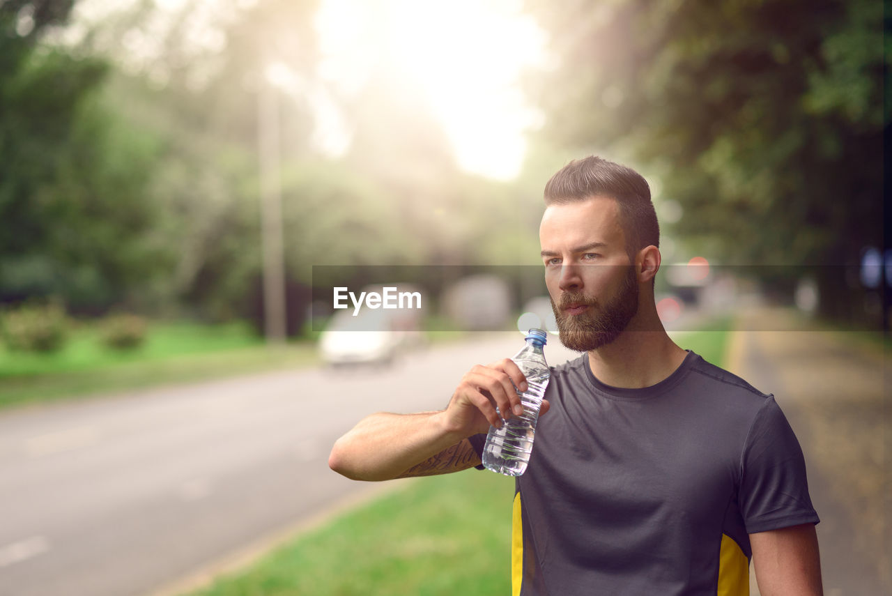 Handsome Athlete Drinking Water By Road
