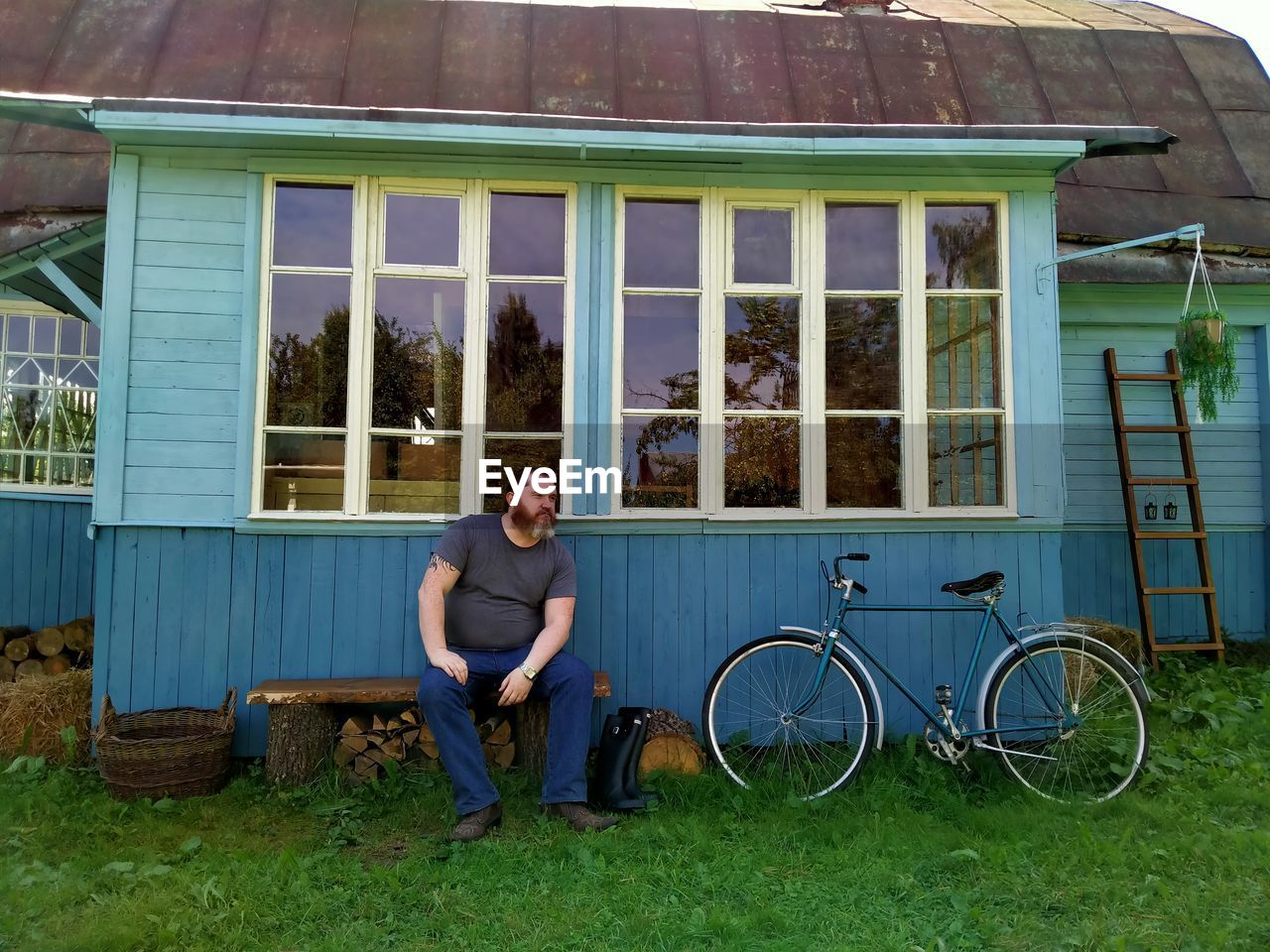 FULL LENGTH OF MAN SITTING ON BICYCLE AGAINST BUILDING