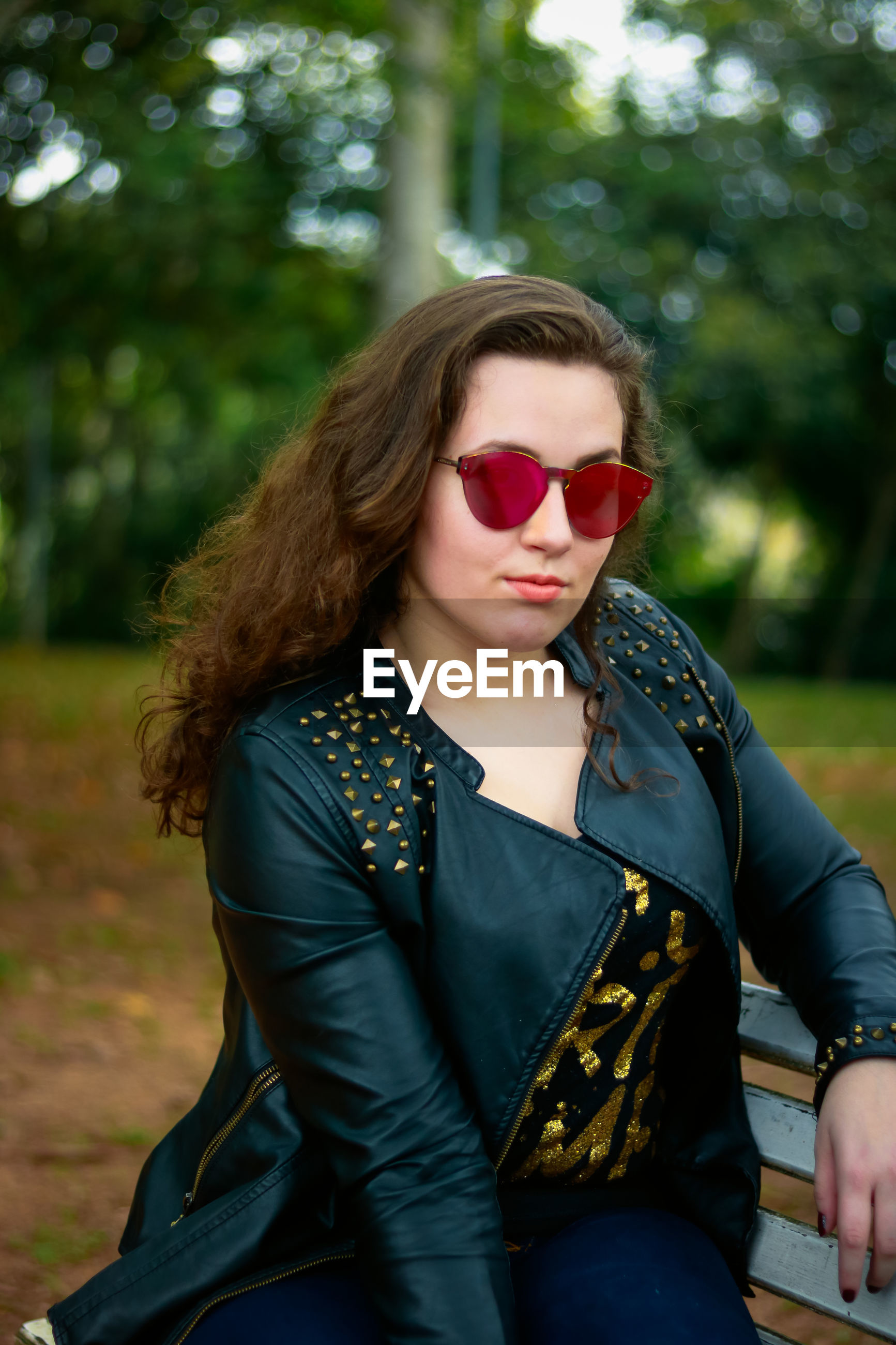 Portrait of woman wearing sunglasses against trees