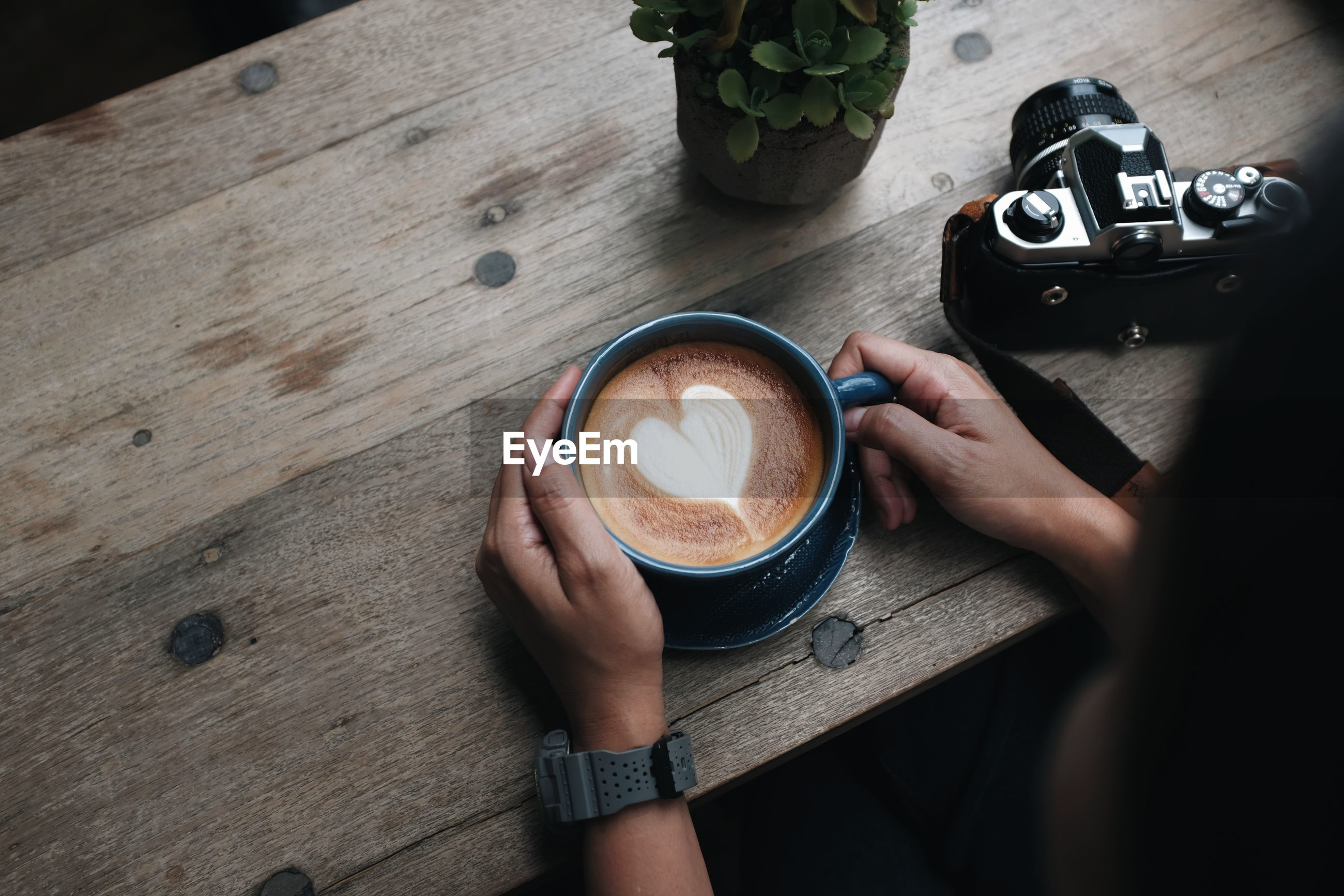 A close up view of a woman's hand holding a latte coffee cup on a wooden table in a coffee shop