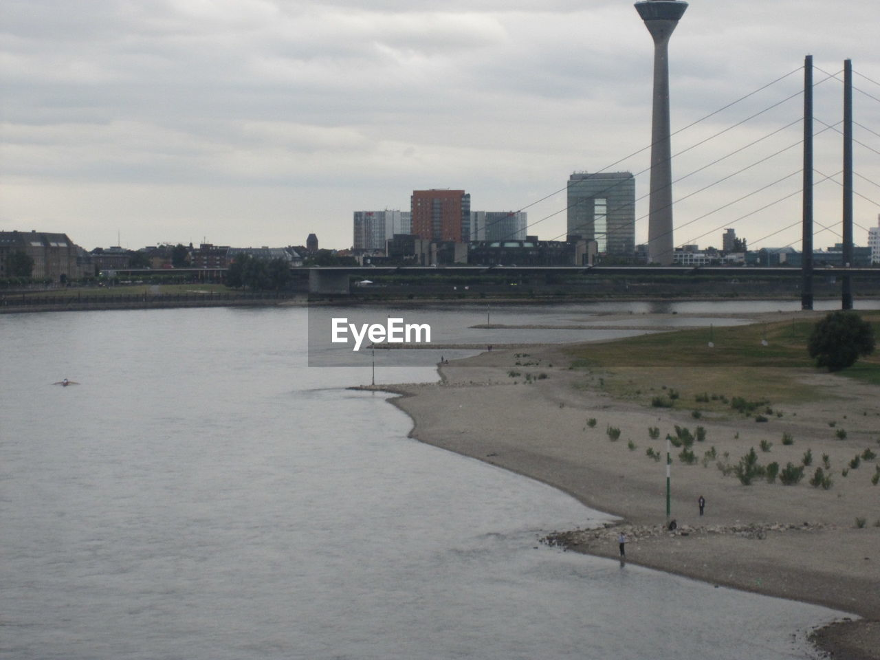architecture, built structure, river, city, skyscraper, sky, building exterior, water, tower, travel destinations, connection, suspension bridge, bridge - man made structure, cityscape, no people, modern, urban skyline, outdoors, day