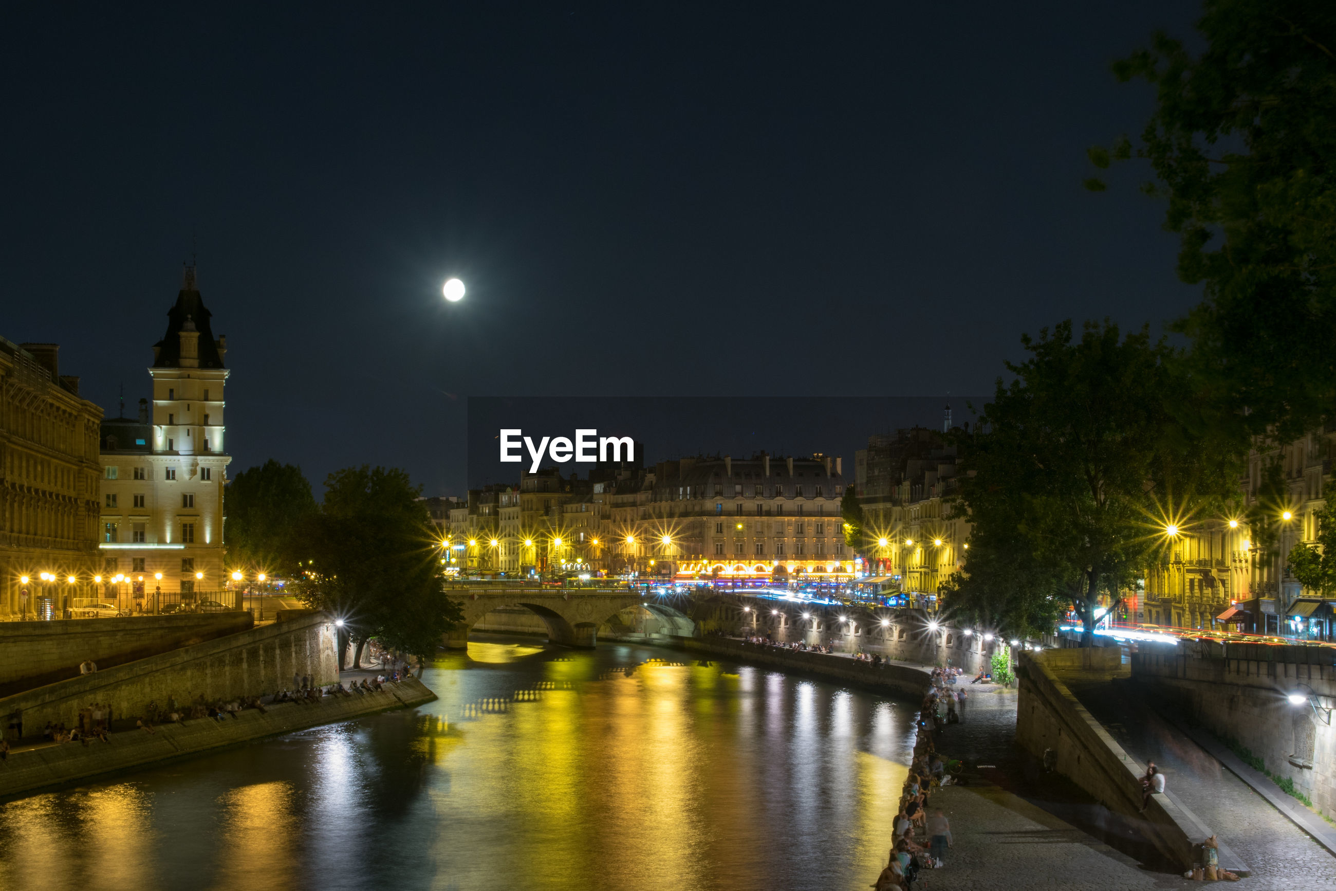 ILLUMINATED BRIDGE OVER RIVER AGAINST BUILDINGS IN CITY AT NIGHT