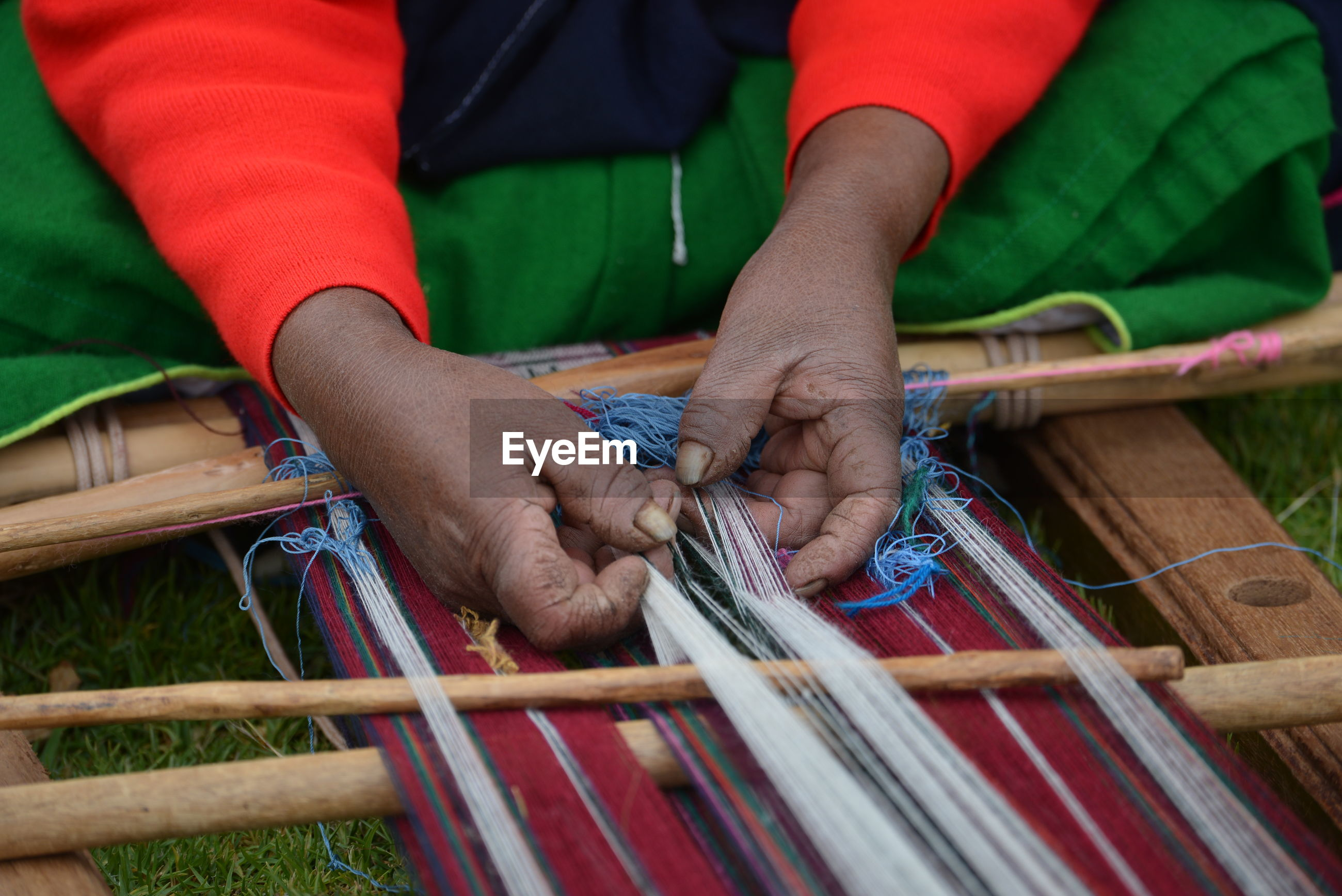 Cropped hands of manual worker weaving textile in workshop