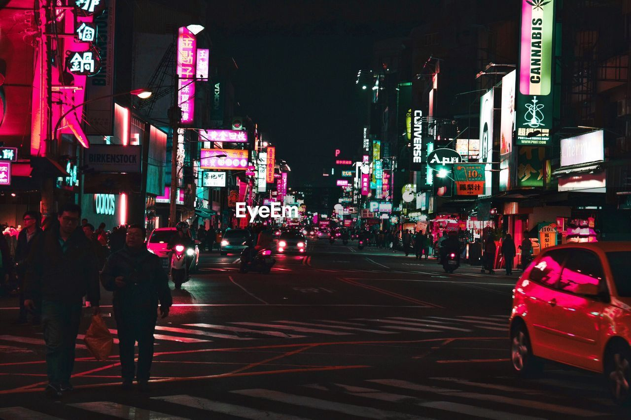 illuminated, night, street, city, building exterior, road, architecture, car, city street, city life, transportation, outdoors, built structure, real people, large group of people, land vehicle, multi colored, neon, group of people, men, crowd, sky, people