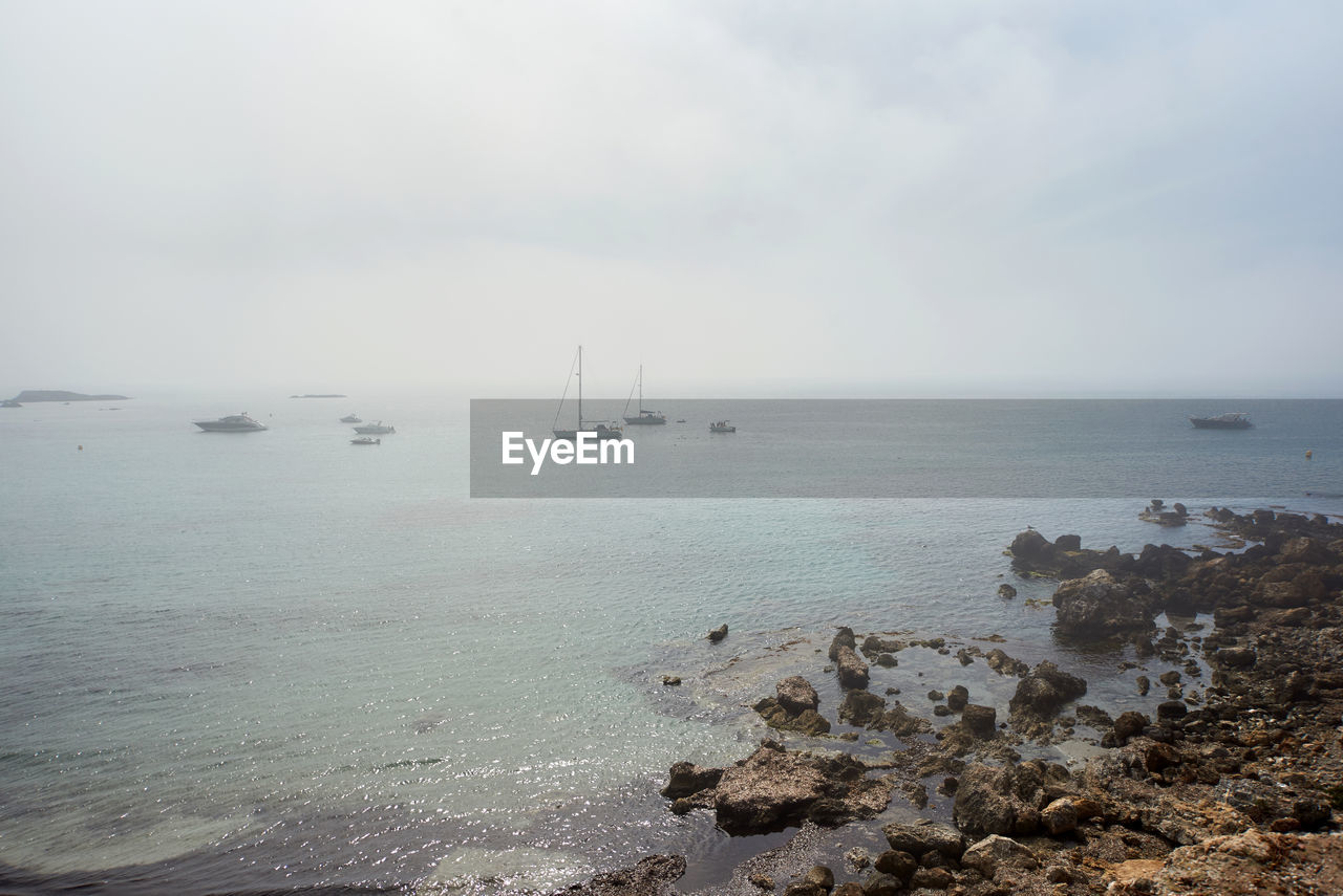 Scenic View Of Beach Against Sky During Foggy Weather