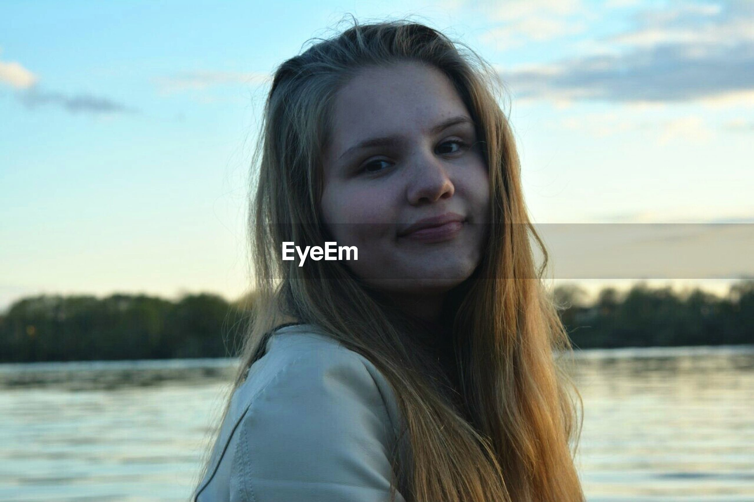 young adult, person, portrait, looking at camera, young women, long hair, lifestyles, water, headshot, focus on foreground, front view, leisure activity, smiling, head and shoulders, sky, casual clothing, brown hair