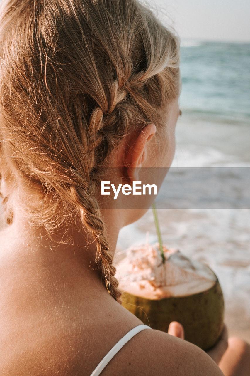 CLOSE-UP PORTRAIT OF WOMAN AT BEACH DURING RAINY SEASON
