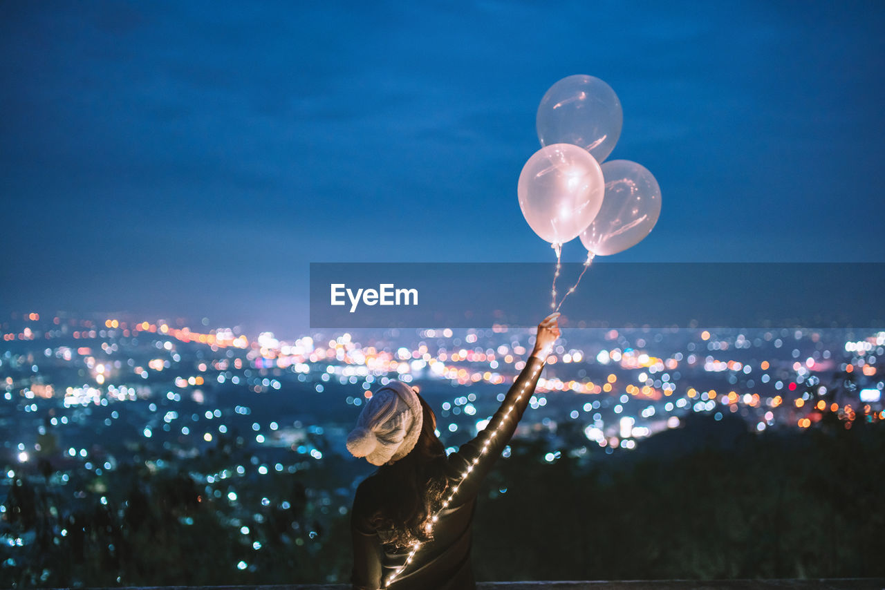 Rear View Of Woman With Arms Raised Holding Balloons While Standing Against Cityscape At Night