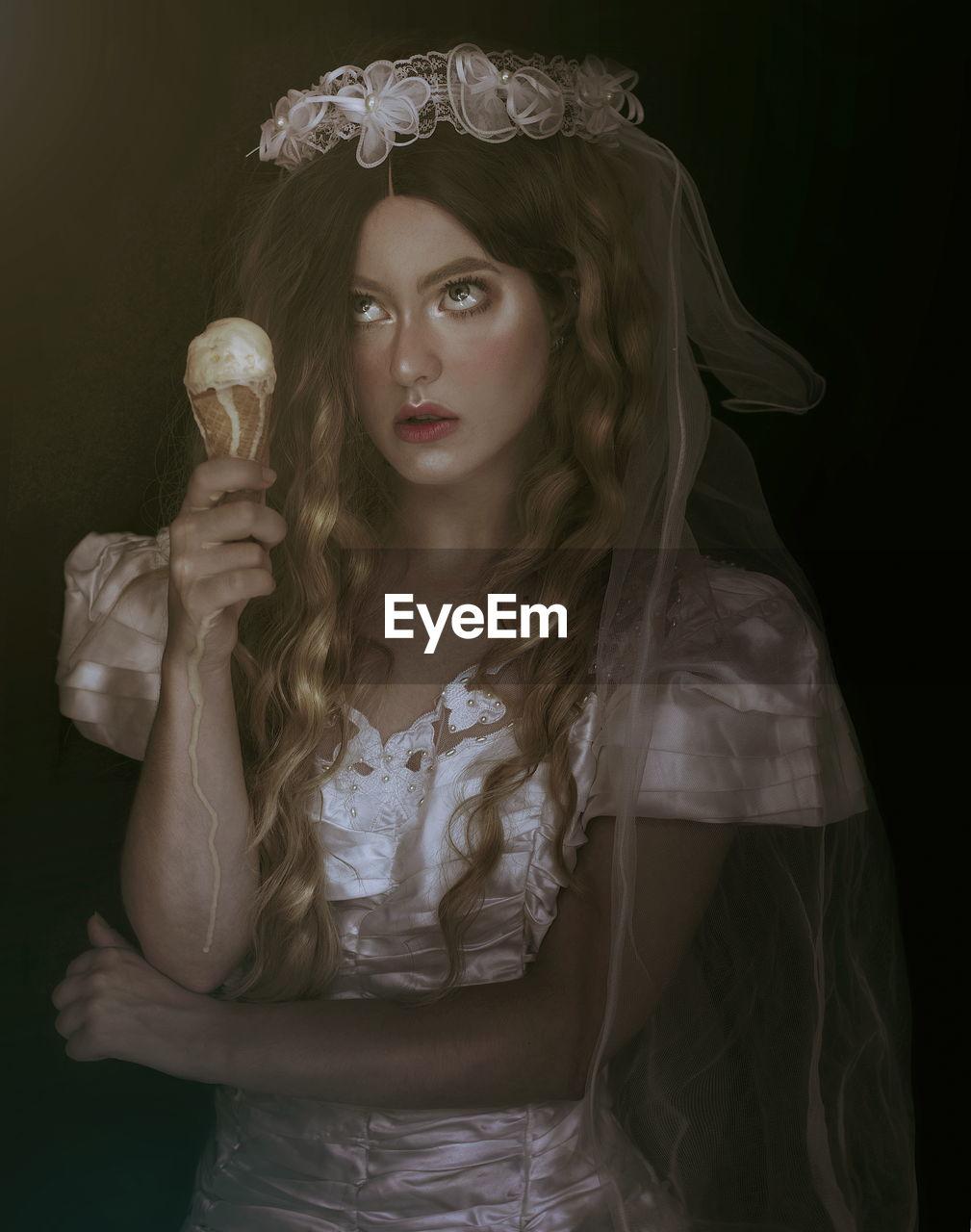 Thoughtful female model in costume having ice cream cone against black background