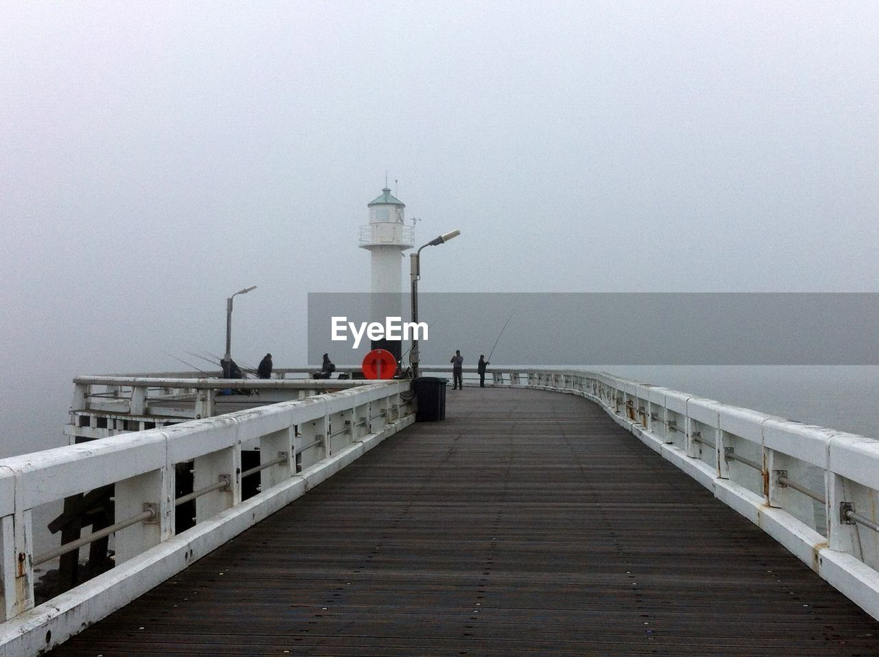 Pier leading towards lighthouse at seaside during foggy weather