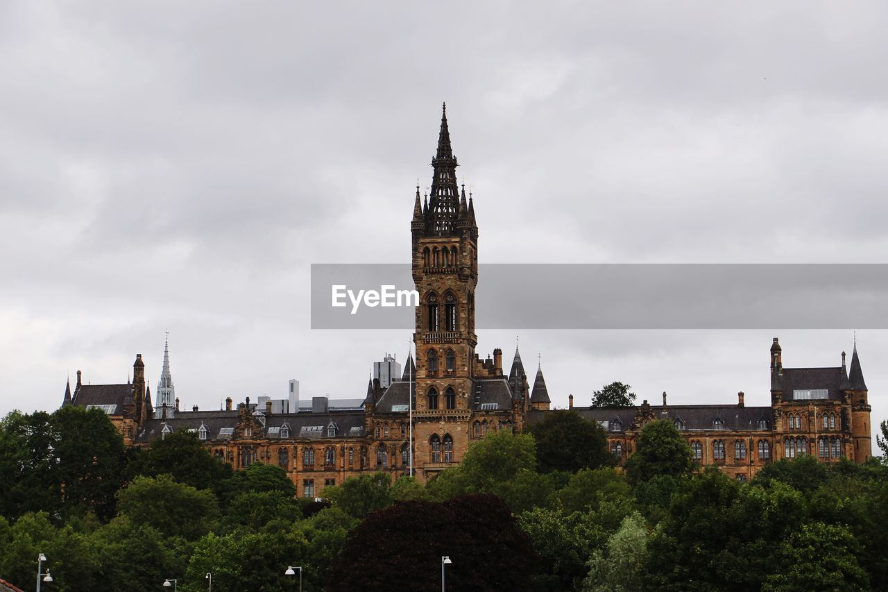architecture, built structure, building exterior, sky, building, tower, tree, cloud - sky, plant, travel destinations, nature, no people, clock tower, travel, history, tourism, city, low angle view, the past, day, outdoors, spire, government, gothic style