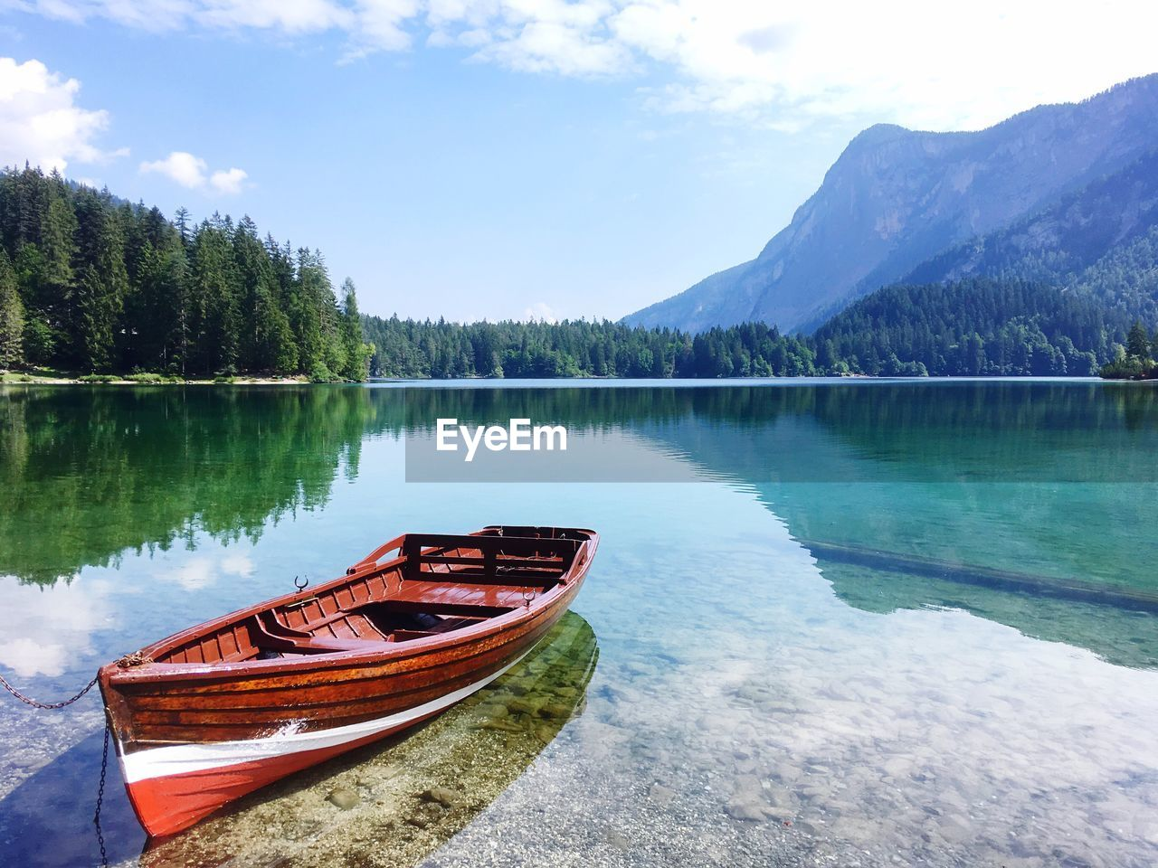 Boat Moored At Lake By Mountains Against Sky