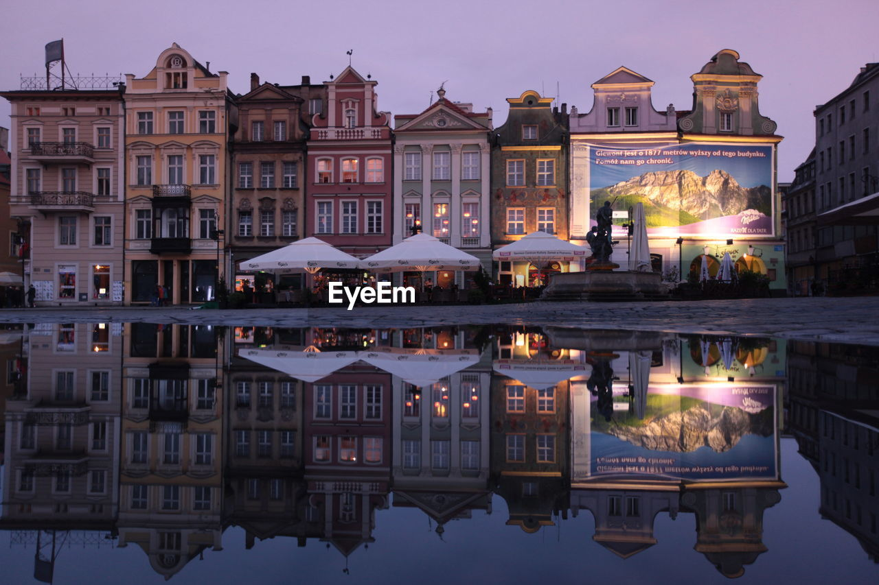 architecture, building exterior, built structure, reflection, water, house, outdoors, waterfront, residential building, sky, illuminated, no people, city, sunset, day