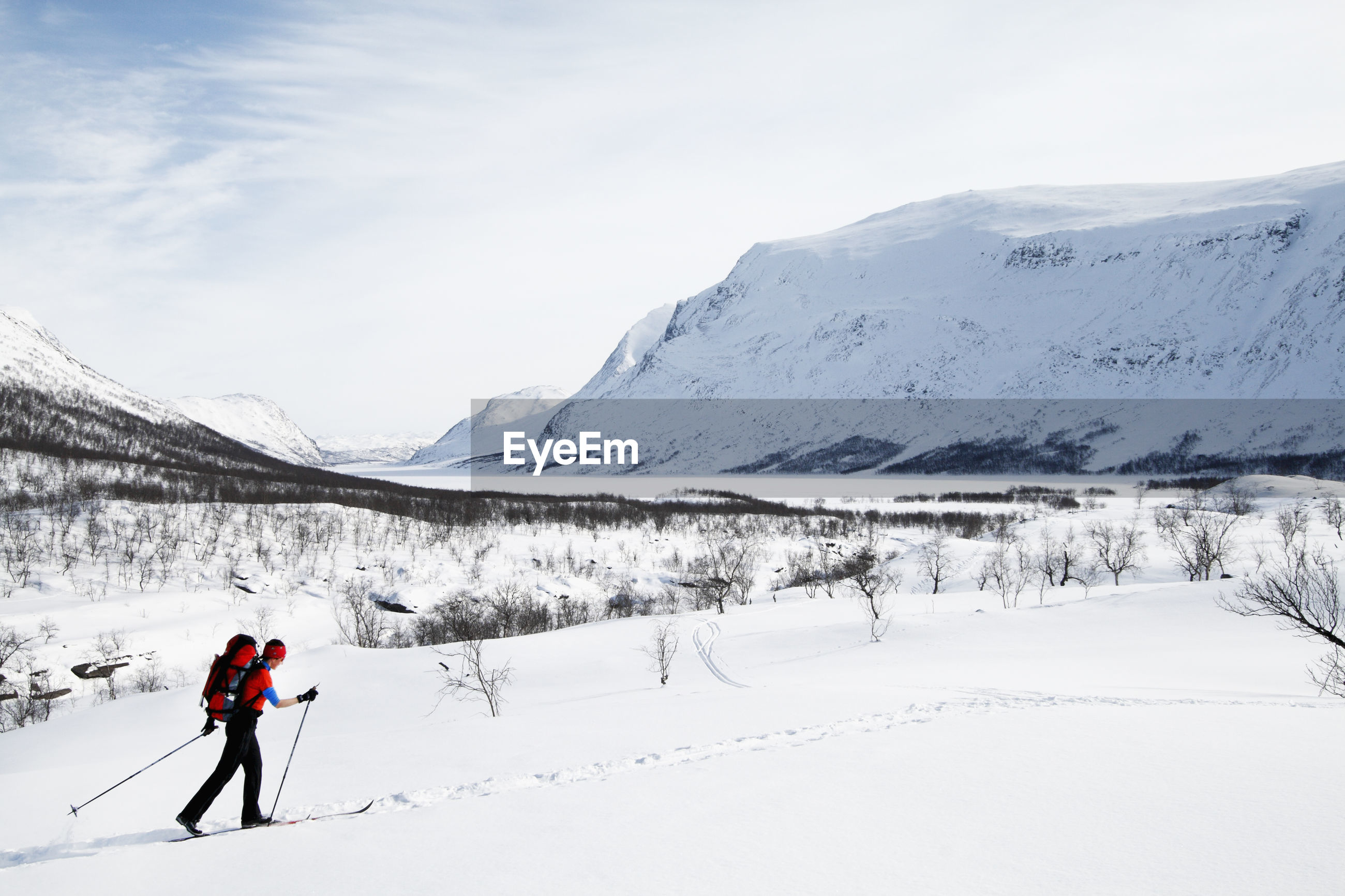 PERSON SKIING ON SNOWCAPPED MOUNTAINS AGAINST SKY