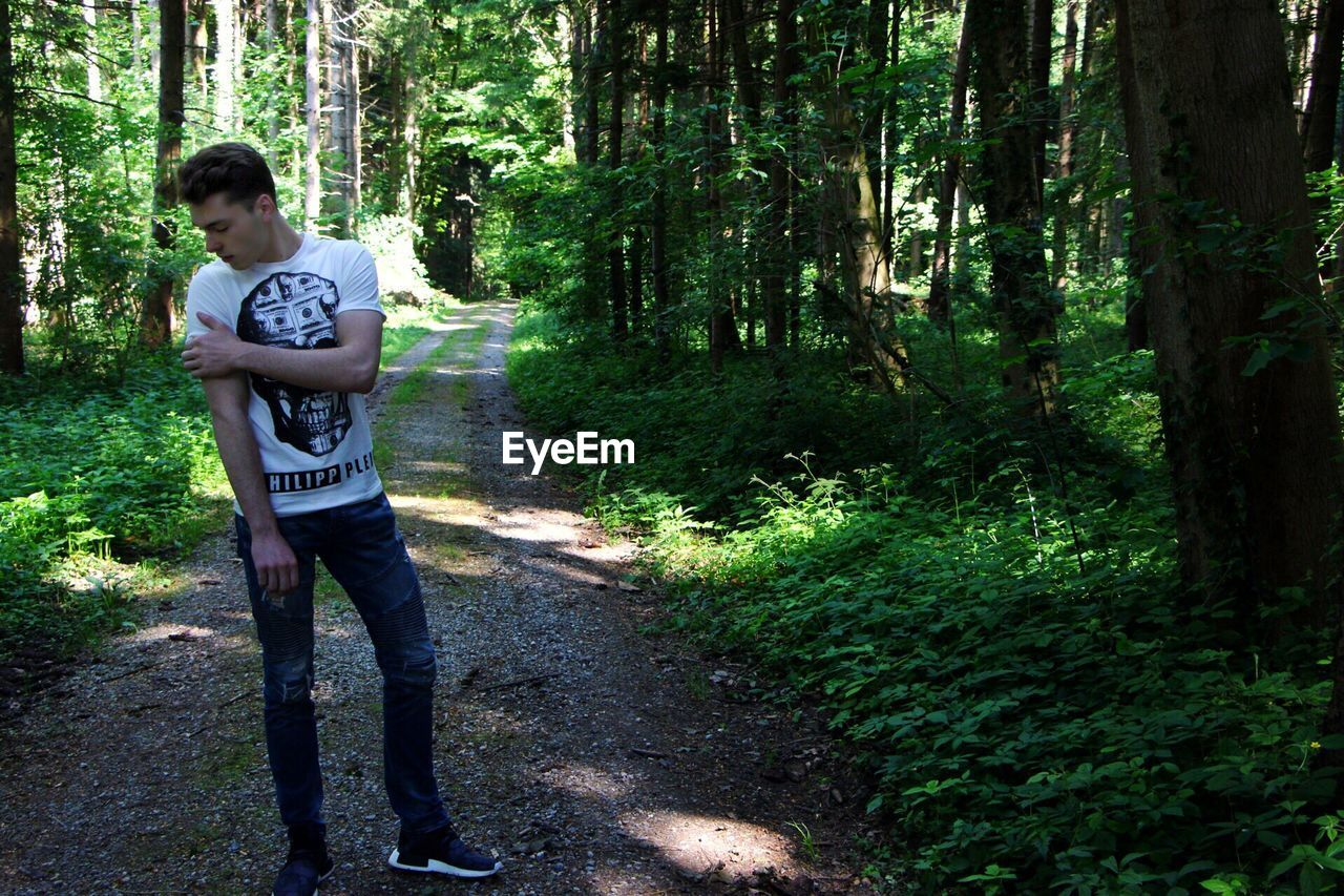 forest, tree, casual clothing, one person, young adult, day, full length, young men, outdoors, nature, standing, one young man only, one man only, people, adults only, adult