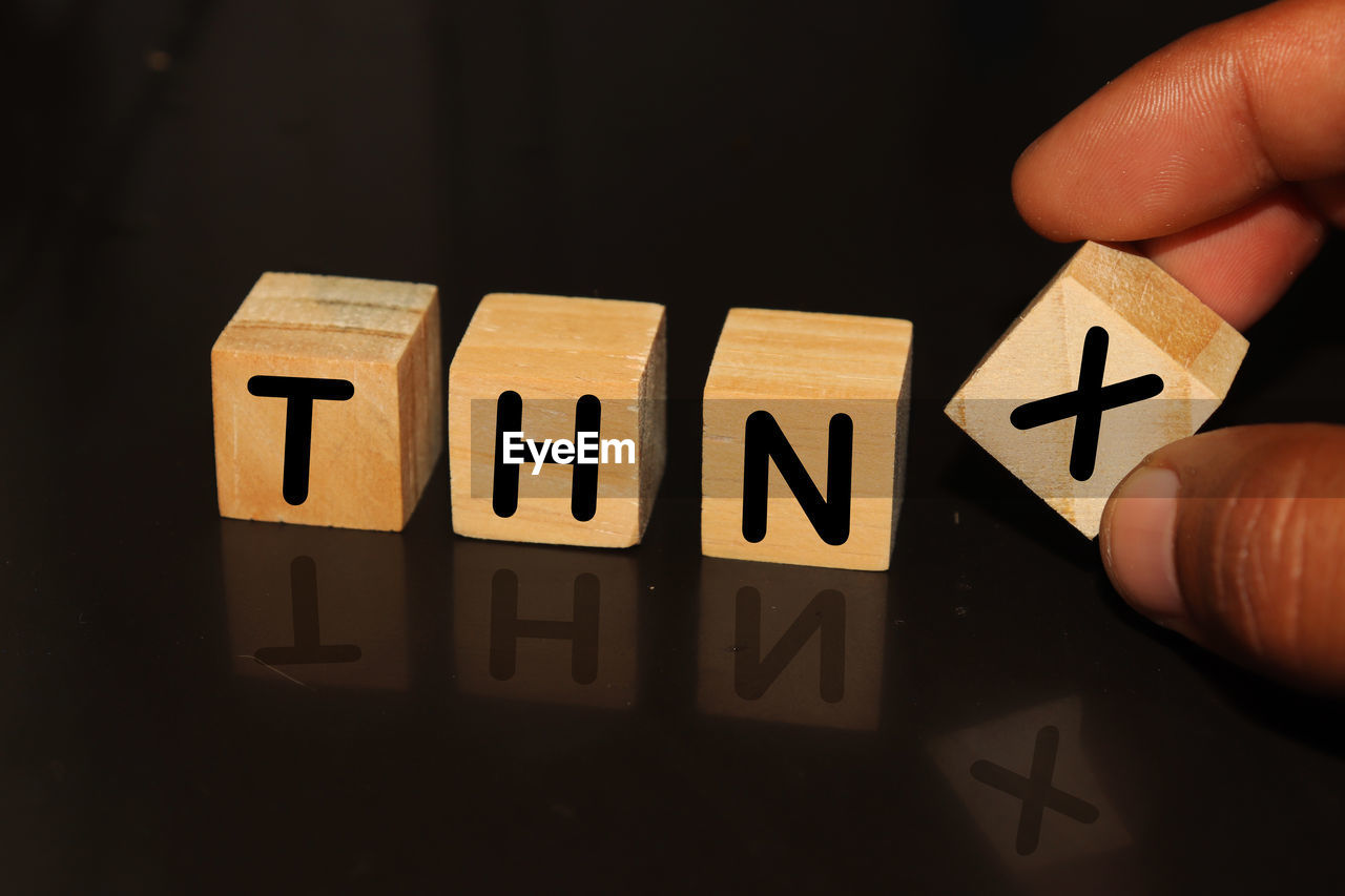Cropped hand with thnx text on toy blocks against black background