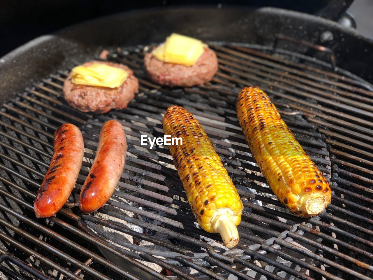 barbecue, food, food and drink, barbecue grill, grilled, preparation, meat, freshness, heat - temperature, close-up, no people, high angle view, sausage, preparing food, healthy eating, focus on foreground, day, metal, wellbeing, vegetable, outdoors, sweetcorn, hot dog, dinner, snack