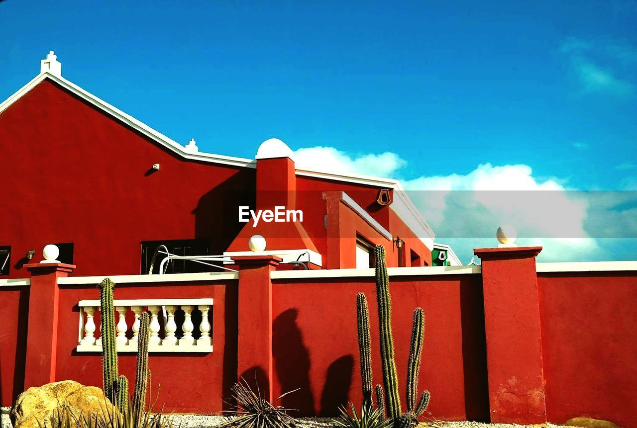 red, sky, architecture, built structure, building exterior, cloud - sky, building, nature, day, no people, blue, sunlight, outdoors, house, low angle view, residential district, city, roof, high section, metal