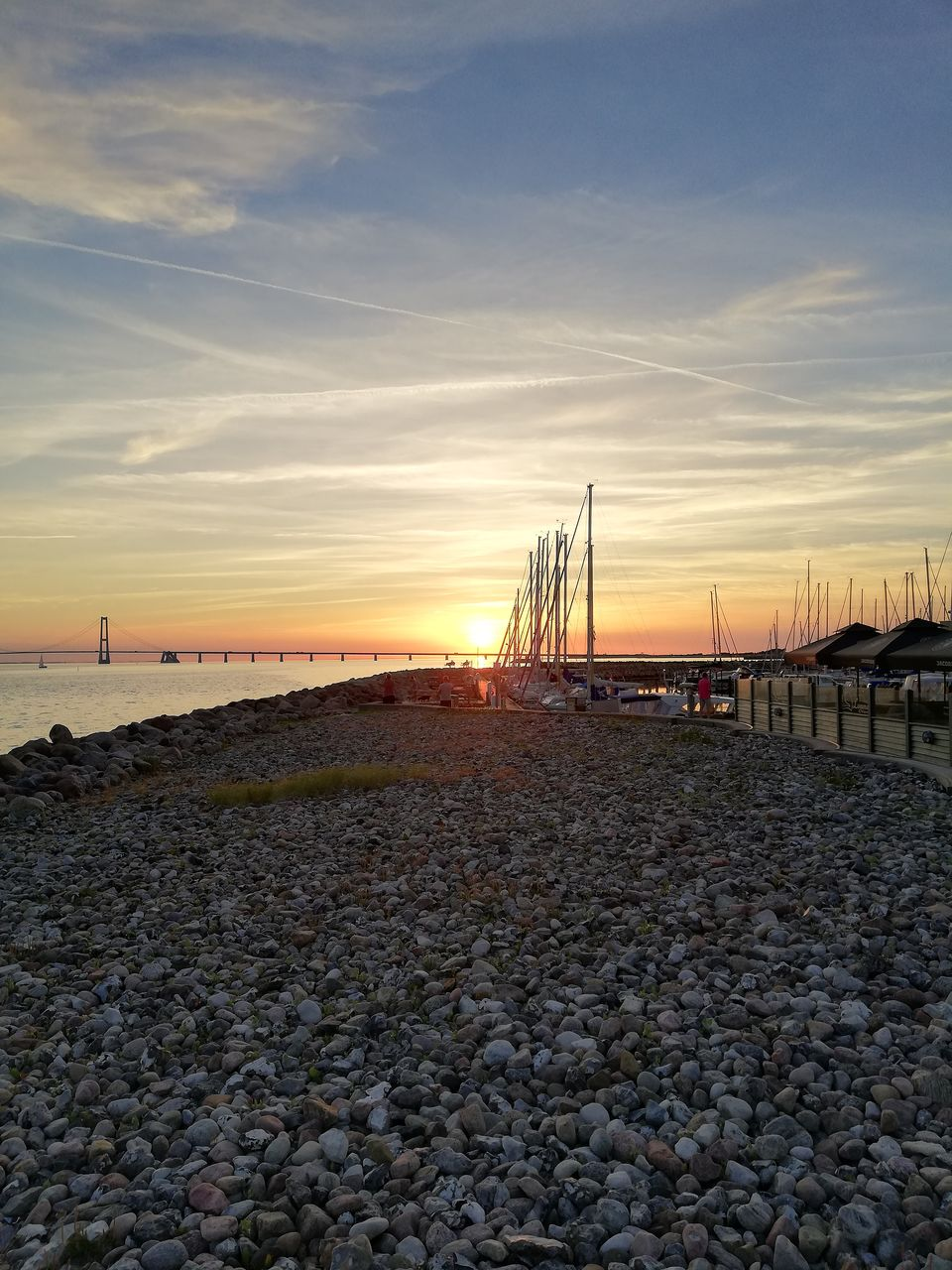 water, sky, sunset, sea, beach, cloud - sky, rock, land, scenics - nature, nature, solid, beauty in nature, stone - object, pebble, tranquil scene, tranquility, stone, rock - object, no people, outdoors, sailboat, groyne