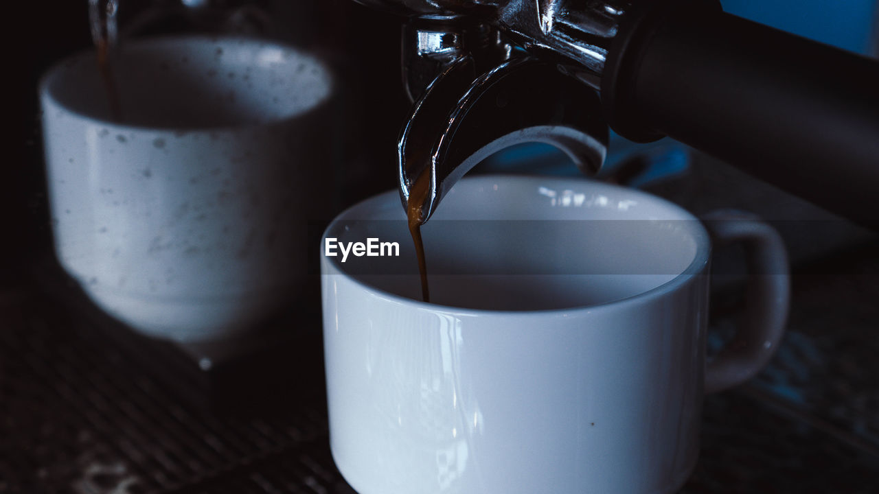 Close-up of machine pouring coffee in cup