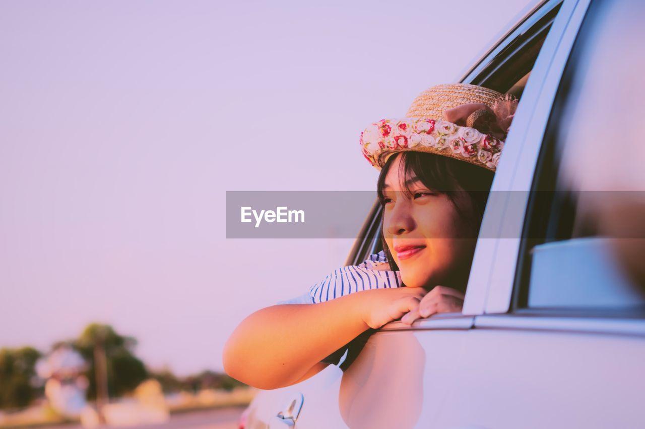 Thoughtful Teenage Girl Leaning On Car Window