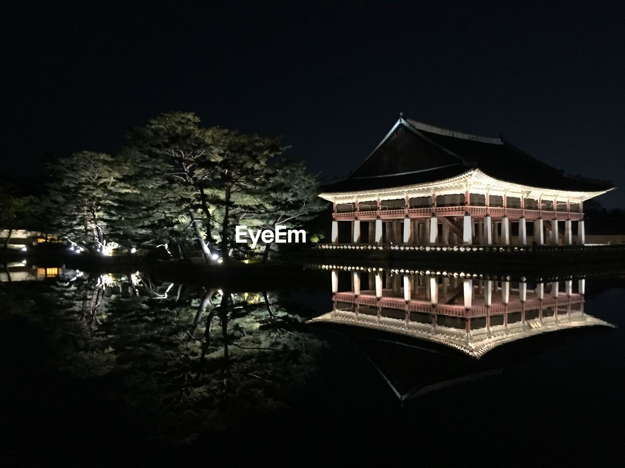 Traditional illuminated building reflecting in lake