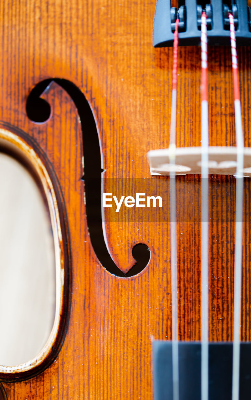 music, musical instrument, wood - material, string instrument, musical equipment, arts culture and entertainment, close-up, indoors, brown, no people, violin, string, musical instrument string, focus on foreground, design, still life, full frame, pattern, table, backgrounds, double bass
